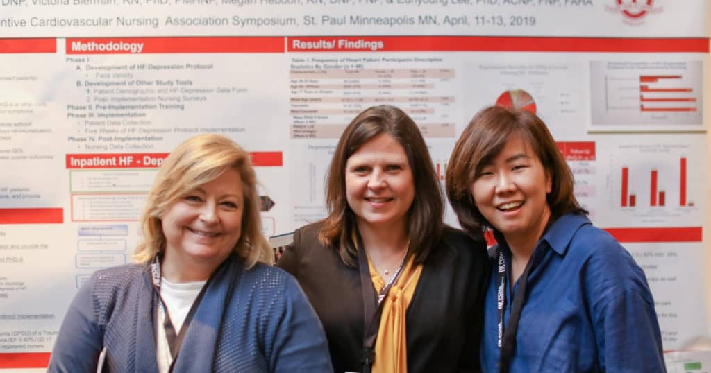 abstract presentation in front of their poster at the cardiovascular nursing symposium