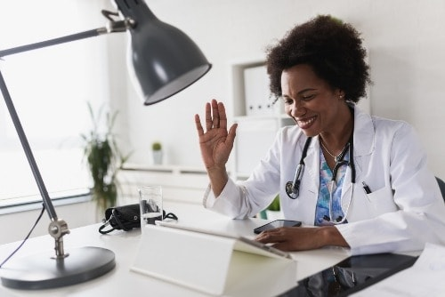 African American health care provider sitting in her office engaging in a telehealth services.