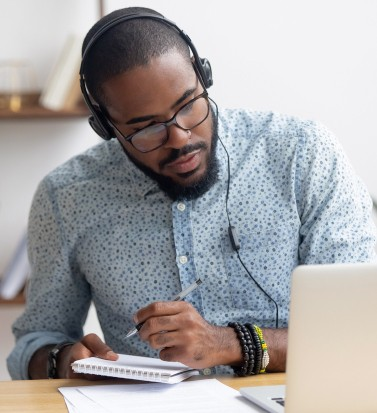 Focused african business man in headphones writing notes in notebook watching webinar video course, serious black male student looking at laptop listening lecture study online on computer e learning (Focused african business man in headphones writing